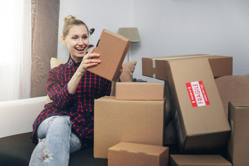 excited woman opening boxes after home delivery