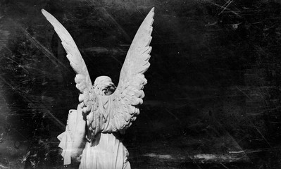 Death and pain concept. Retro styled antique statue of an angel against black background.