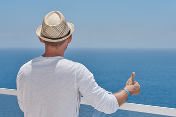 e28bede130f European man in sun hat is observing wonderful hotel s view. He is enjoying  his vacations