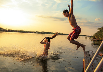 Group of friends jumping into the lake from wooden pier.Having fun on summer day.
