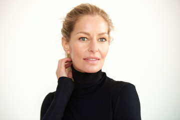Attracitve mature woman close-up portrait while standing at isolated white background