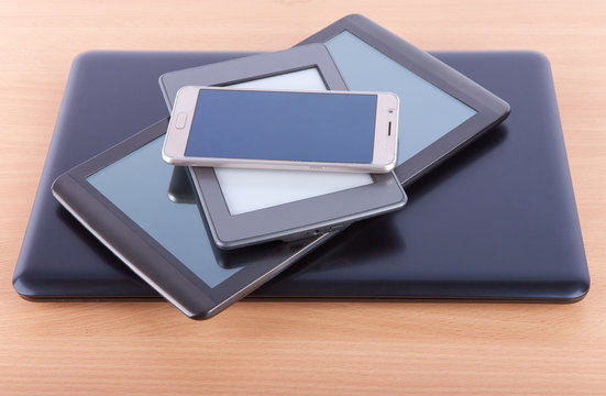 Stack made from notebook, tablet, ebook reader and a smatphone on a desk