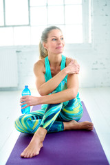 Beautiful sporty woman relaxing after yoga workout on yoga mat