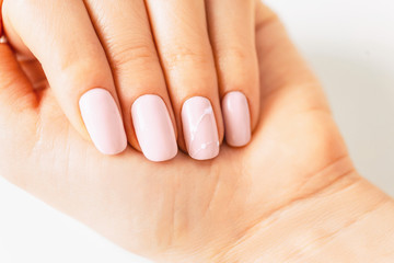 Woman's hand with manicure of pink pastel color and art design, close-up.
