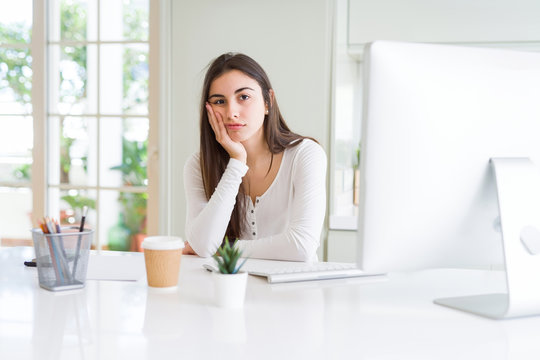Beautiful young woman working using computer thinking looking tired and bored with depression problems with crossed arms.