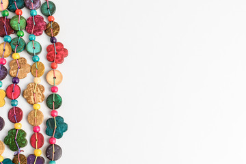 Multi coloured beards hand made from coconut shell flower and rounded pieces, traditional African decoration isolated on white background, top view with copy space