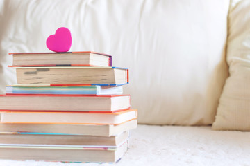 Stack of books and pink heart on the white bed. Education background with Copy space, back to school concept