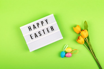 Easter composition, greeting card with lightbox text Happy Easter, colored decorative eggs, yellow tulips on color background.