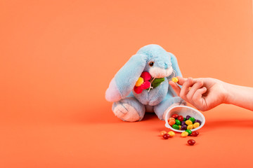 Child hand feeds the Easter rabbit sweet multicolored dragee on coral background. Decorative Easter festive composition, greeting card.