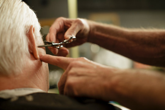 Close up of barber trimming senior man's hair