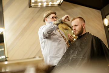Barber styles man's hair