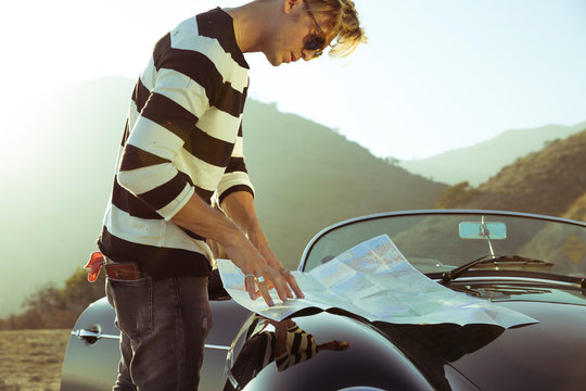 Stylish young man looks at map on convertible