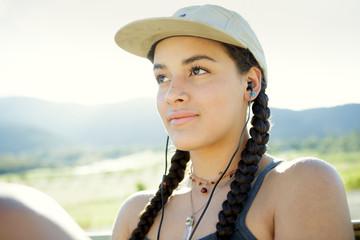 Young woman wears baseball cap and headphones
