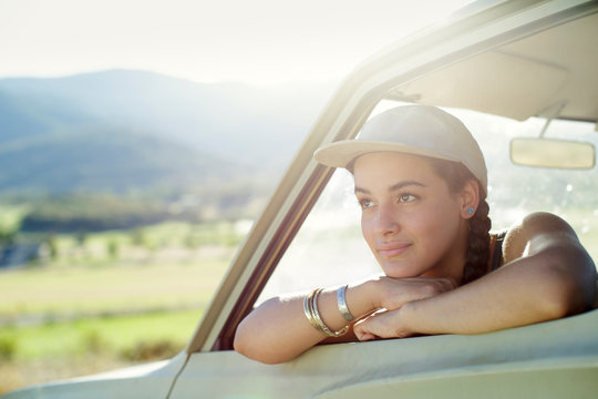 Young woman wears baseball cap and leans out car window