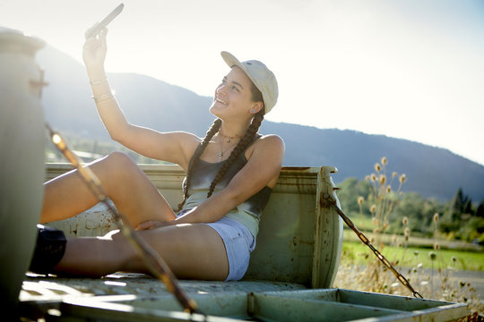 Young woman in baseball cap takes selfie in pickup truck