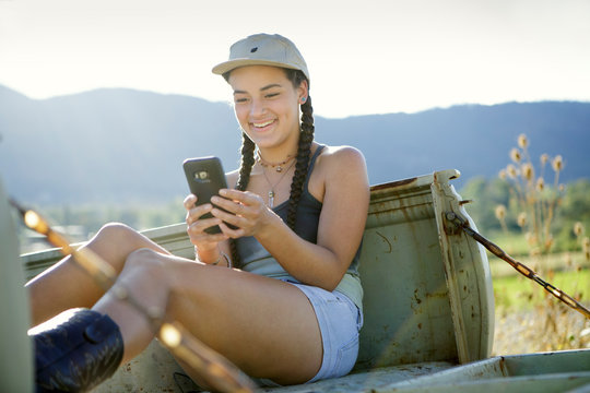 Young woman looks at mobile phone while sitting in pickup truck