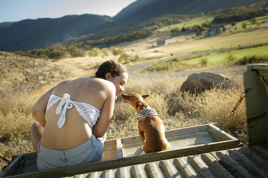 Young woman touches noses with pet chihuahua
