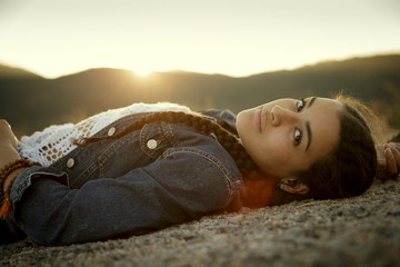Young woman relaxes by mountains at sunset