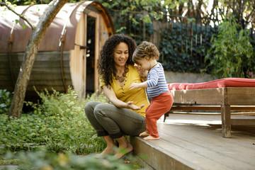 Mother helps toddler step off deck