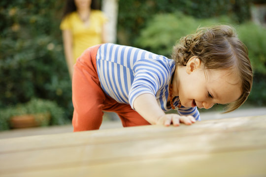 Toddler finds something exciting under deck