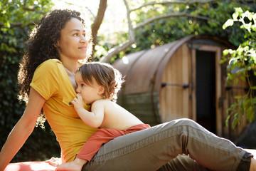 Toddler breastfeeds in backyard