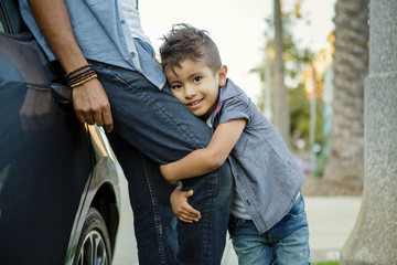 Young boy with mohawk hugs father's leg