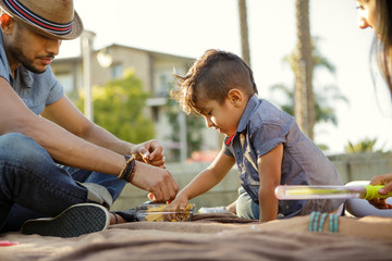 Young boy with mohawk and father eat snacks
