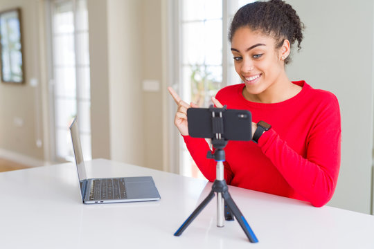 Young african american woman doing video call using smartphone camera smiling and looking at the camera pointing with two hands and fingers to the side.