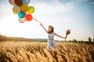 Girl with colorful balloons walking in wheat field