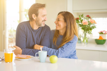 Beautiful romantic middle age couple having healthy breaskfast in the morning at home Wall mural