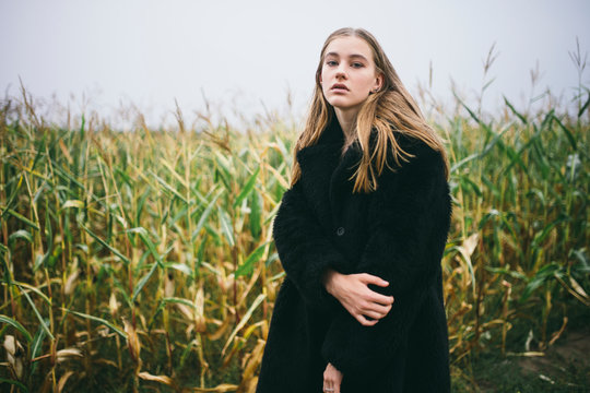 woman stands in a corn field in cloudy weather