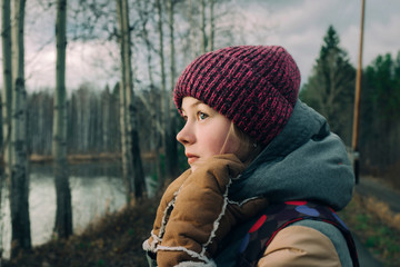 Beautiful girl in warm clothes in the forest