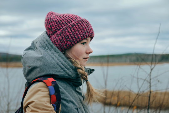 Side view of teenage girl wearing knit hat standing outdoors