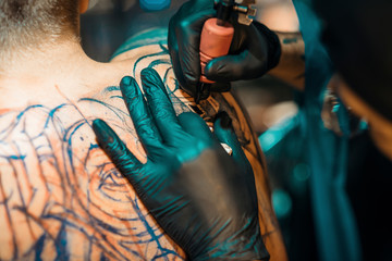 Closeup Of Male Tattoo Master In Black Gloves Tattooing Male Back In Tattoo Salon