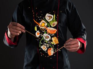 Foto op Aluminium Sushi bar Master chef holding chopsticks with flying sushi