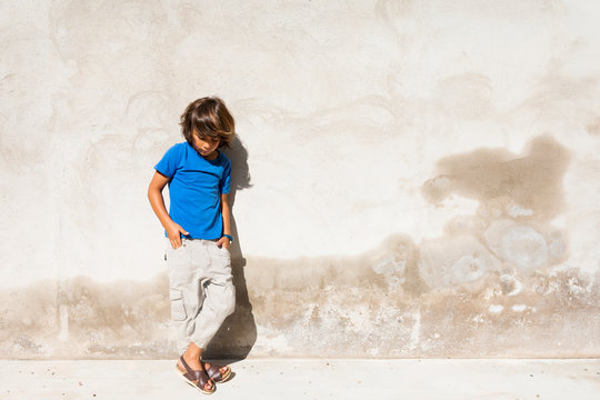 Boy leaning on wall outdoors