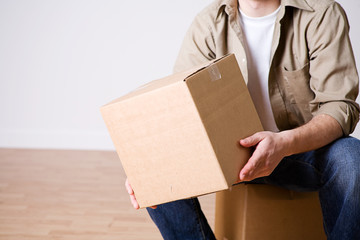 Moving: Man Sitting With Packed Cardboard Box