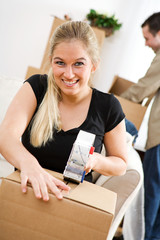 Moving: Smiling Woman Tapes Up Box