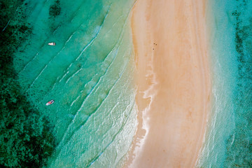 Sea and beach aerial view, Top view,amazing nature background. Beautiful strip of white sand surrounded by crystal clear water with boats