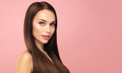 Beautiful Brown hair model face portrait. Elegant attractive woman with pergect skin and natural make up against pink bacground. Beauty salin and cosmetics concept. Banner with copy space.