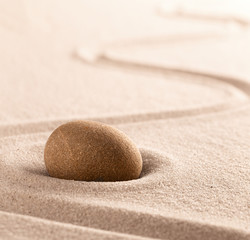 Yoga or zen Buddhism stone and sand background. Concentration or focus point for spiritual balance and purity of mind and soul. Sandy background with copy space. .