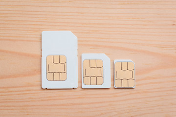 SIM cards of different side on a wooden background. SIM card, micro SIM and nano SIM on table