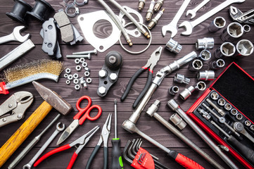 tools and auto spare parts on wooden workbench