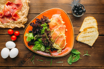 Meat salad, olives, bread and eggs on wooden table