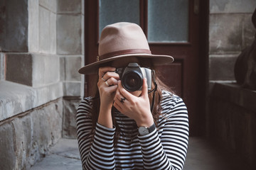Young beautiful woman in hat is taking picture with old fashioned camera, outdoors