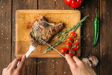 Female hands cuts juicy steak piece