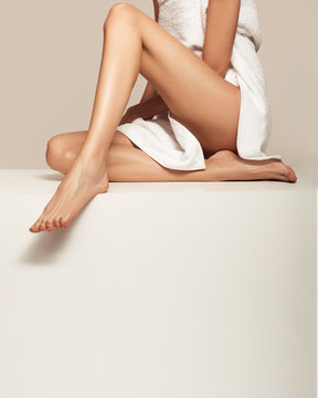 Beautiful long legs of a woman. Sitting wrapped in a white terry towel