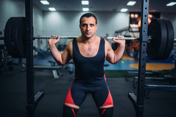 Athlete prepares to make squats with barbell