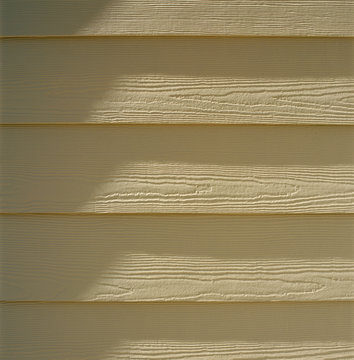 Close up detail of painted engineered composite wood siding. Home construction building materials backgrounds elements.