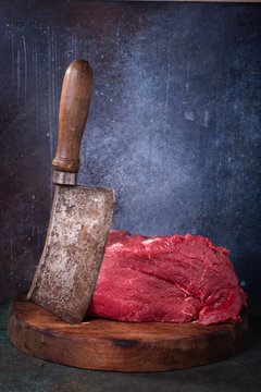 Raw beef and meat cleaver on cutting board on grunge background vertical. With copy space